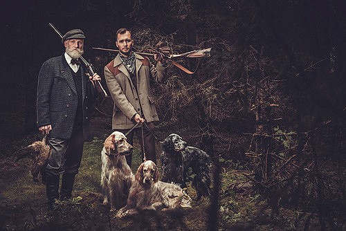 Two hunters with dogs and shotguns in a traditional shooting clo